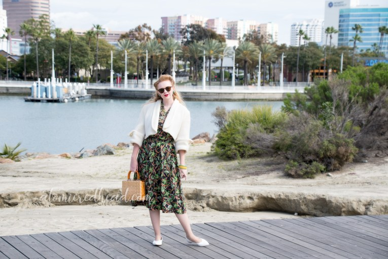 Myself standing in front of a harbor, wearing a white cropped bolero, and a navy two piece set featuring a print of shells and starfish in green and orange.