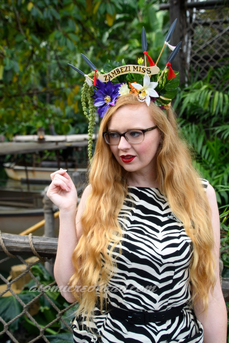 """Atop my head sits a headpiece made of tropical green leaves, purple, white and yellow flowers, and spears. Across the middle a small arched sign reads """"Zambezi Miss."""" I wear a sleeveless dress featuring zebra print. Bamboo bangles grace the wrists."""