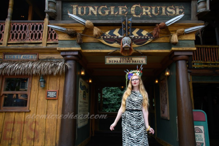 Standing in front of the entrance to the Jungle Cruise, wearing a sleeveless zebra print dress.