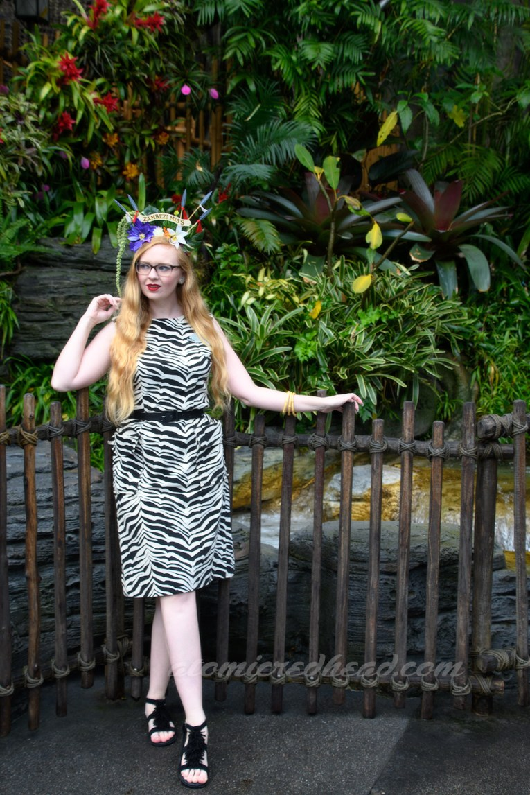 Standing in front of a small waterfall that is enveloped by tropical vegetation, wearing a zebra print dress.