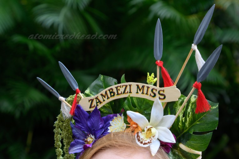 """Close-up of my headpiece, featuring large green tropical leaves, a large purple flower, and smaller white and orange flowers. Five spears jut from the middle, and a small arched sign reads """"Zambezi Miss"""" in dark green letters."""