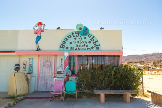 "The outside of the Beauty Bubble, a cream building with orange sherbet trim, a large half circle painted turquoise reads ""The Beauty Bubble Salon and Museum"" with small bubble like circles rising from it. A cartoon of a woman is painted next to it, who does her hair with hair spray while looking in a mirror. Outside sit a blue and a pink chair, and on the left a sauna hair dryer."