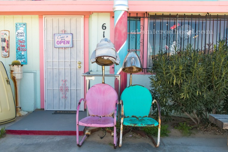 A bright pink and a turquoise chair sit outside the door to the Beauty Bubble, each have hair dryers above them.