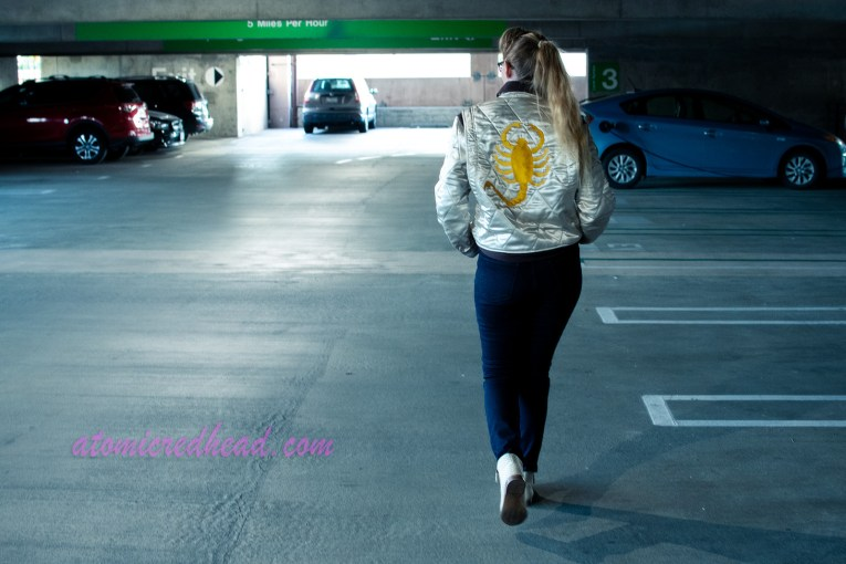 Myself, walking away from the camera, down through the parking structure, the back of the jacket visible, featuring a gold embroidered scorpion.