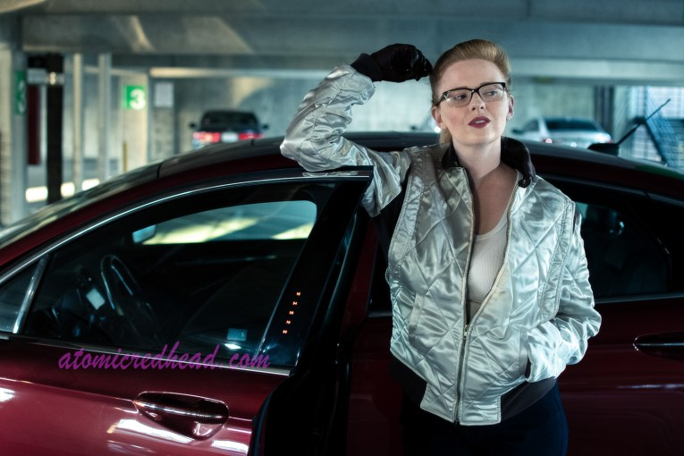 Myself, wearing a silver jacket, white shirt, and skinny dark blue jeans, leaning up against the open door of a red car in a parking structure.