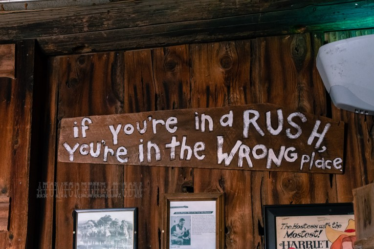 "A painted wooden sign reads ""If you're in a rush you're in the wrong place"""
