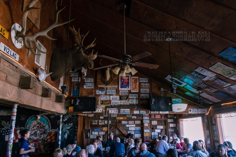 Moose and deer head mounts hang from the wood paneled walls along with old license plates.