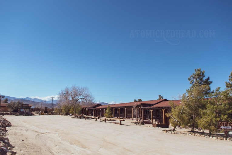 A long, single story building stretches into the distance under a blue sky. The building is akin to a log cabin.