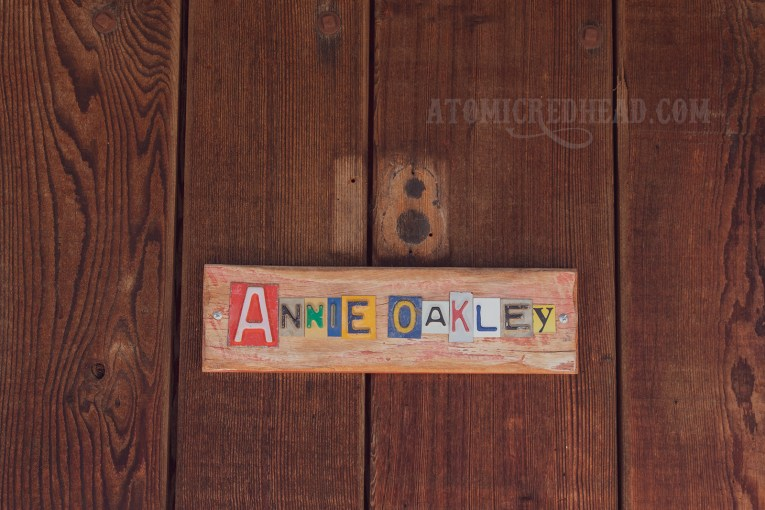 """Cut out letters from old license plates spell out """"Annie Oakley"""""""