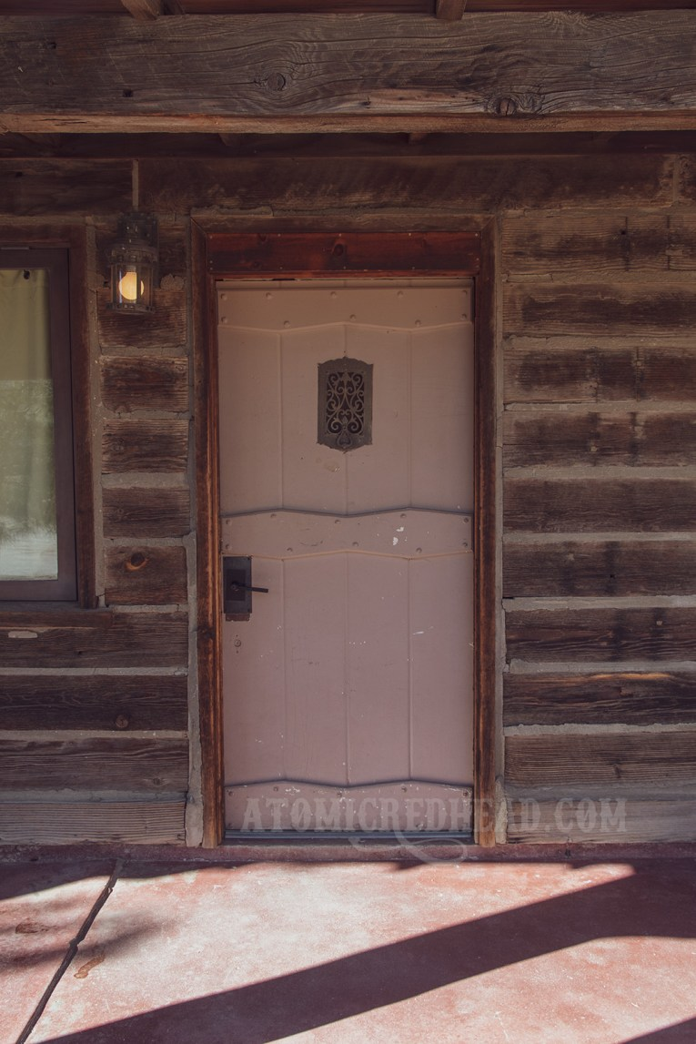 A mauve colored wooden door features an iron peek window.