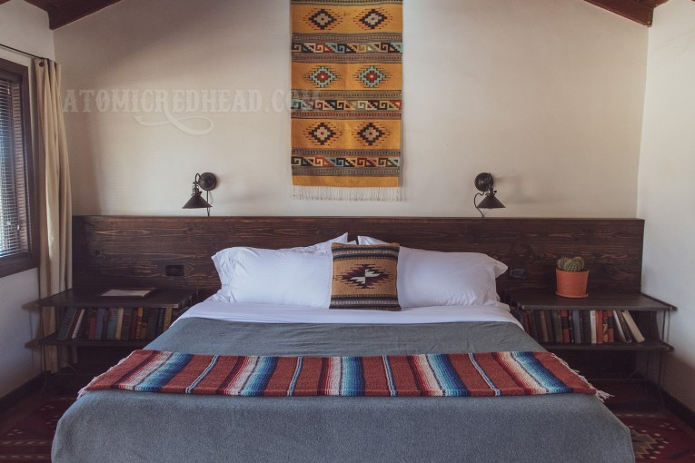 Inside our room, on a white wall above the bed hangs a yellow and red Indian blanket. The bed features a pillow also of an Indian blanket, and the bed has a grey wool blanket and another Indian blanket at the food.