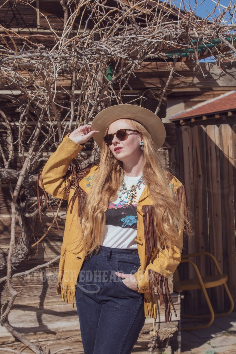 """Myself standing in front of part of the Pioneertown Motel, wearing a butter yellow leather jacket with dark brown fringe, a t-shirt featuring the cover of the Eagles' album """"Hotel California,"""" jeans, and a cream colored flat top cowboy hat."""