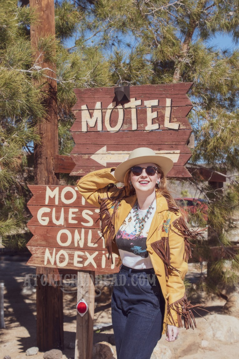 """Myself standing in front of the sign for Pioneertown Motel, reading """"Motel Guests Only,"""" wearing a butter yellow leather jacket with dark brown fringe, a t-shirt featuring the cover of the Eagles' album """"Hotel California,"""" jeans, and a cream colored flat top cowboy hat."""