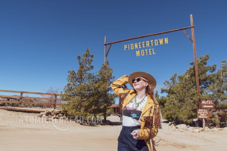 "Myself standing in front of the Pioneertown Motel sign, wearing a butter yellow leather jacket with dark brown fringe, a t-shirt featuring the cover of the Eagles' album ""Hotel California,"" jeans, and a cream colored flat top cowboy hat."