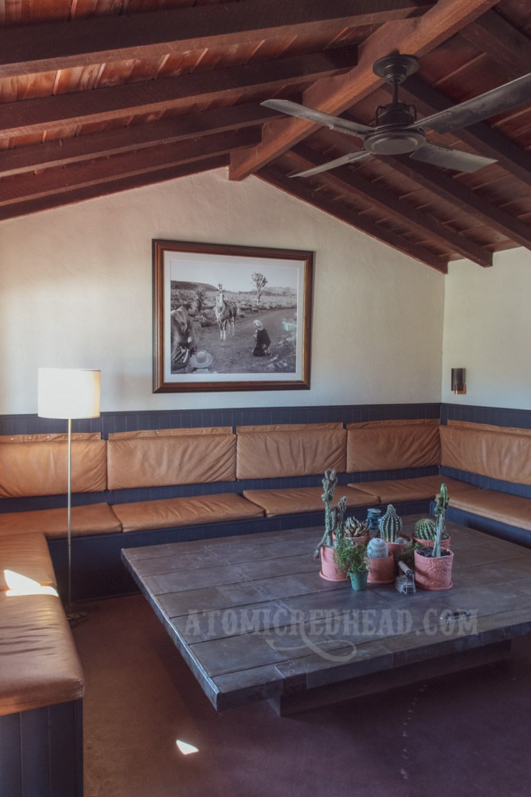 The inside of the common room, which features upholstered seats all the way around it, and a massive coffee table in the center. Hanging on the wall is a photograph of a cowboy and his horse.