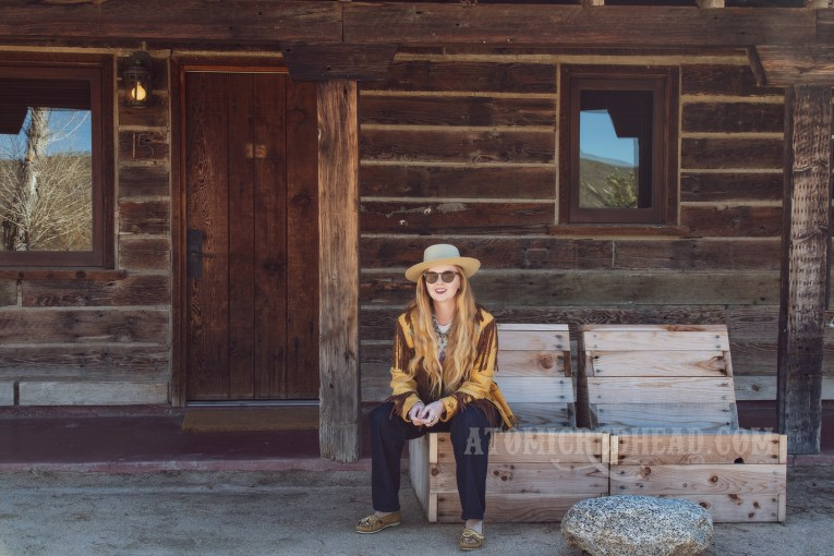 """Myself sitting in front of part of the Pioneertown Motel, wearing a butter yellow leather jacket with dark brown fringe, a t-shirt featuring the cover of the Eagles' album """"Hotel California,"""" jeans, and a cream colored flat top cowboy hat."""