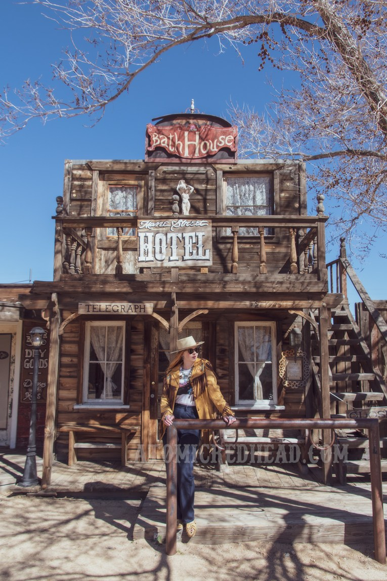 "Myself standing in front of one of the Pioneertown facades, the ""Mane Street Hotel and Bath House"" wearing a butter yellow leather jacket with dark brown fringe, a t-shirt featuring the cover of the Eagles' album ""Hotel California,"" jeans, and a cream colored flat top cowboy hat."