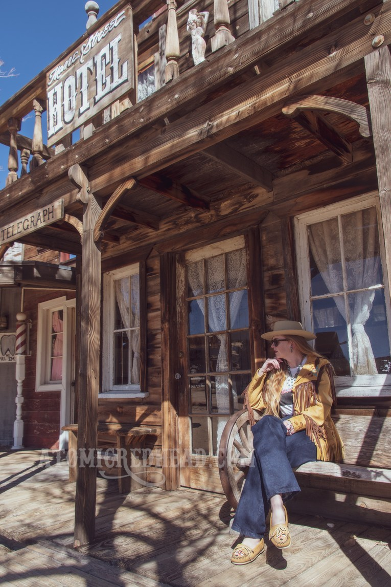 """Myself sitting in front of one of the Pioneertown facades, the """"Mane Street Hotel and Bath House"""" wearing a butter yellow leather jacket with dark brown fringe, a t-shirt featuring the cover of the Eagles' album """"Hotel California,"""" jeans, and a cream colored flat top cowboy hat."""