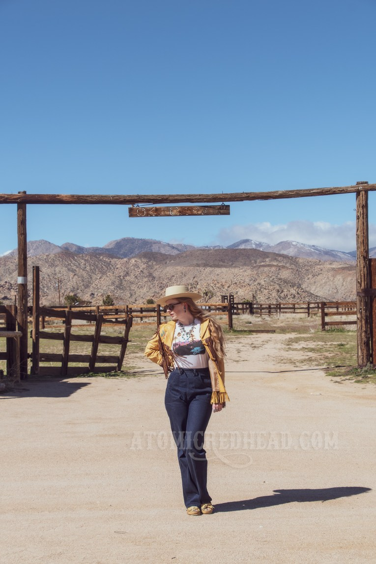 """Myself standing in front of a horse corral wearing a butter yellow leather jacket with dark brown fringe, a t-shirt featuring the cover of the Eagles' album """"Hotel California,"""" jeans, and a cream colored flat top cowboy hat."""