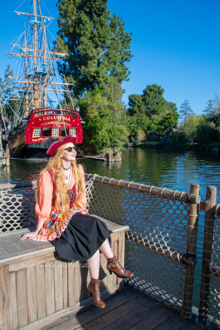 Myself, wearing a dress with peach sleeves, maroon corset, and floral skirt, worn over a black skirt to the knee, and a maroon pirate hat, sitting in front of Disneyland's Sailing Ship Columbia.