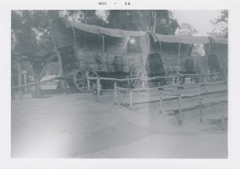 A black and white photo of of the covered wagons that guests can sit in in the Wagon Camp theater.