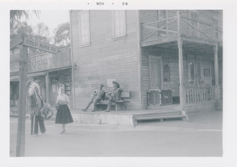 A black and white photo of the Gold Trails Hotel, a two story building. Statues of cowboys sit out front. A man in a Native American headdress stands on the left.