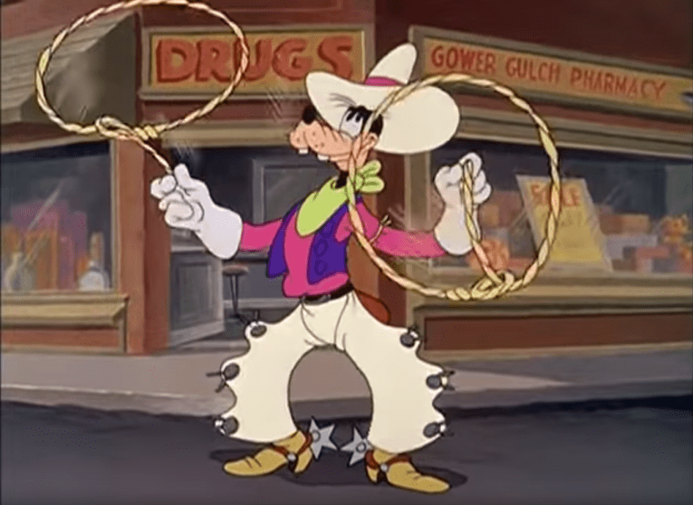 "Goofy stands in a magenta shirt, purple vest, tan chaps, and tan cowboy hat, twirling two ropes, one in each hand, in front of a drugstore titled ""Gower Gulch Drugstore"""