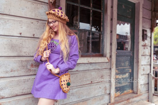 Myself standing on the porch of a small western style home, wearing a short, long sleeved purple dress with a large boysenberry embroidered on the front, a boysenberry pie hat, and a boysenberry pie purse.