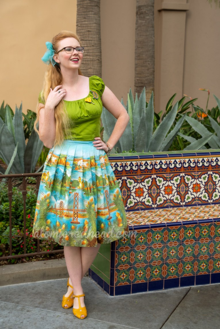 Myself standing in front of an adobe colored building and mosaic tile bench, wearing a green peasant top, with a D shaped brooch, and a poppy flower brooch, and a skirt featuring images of the San Fransisco-Oakland Bay Bridge, Catalina, and Mission Santa Barbara, a blue scarf is tied in my hair, and yellow shoes.