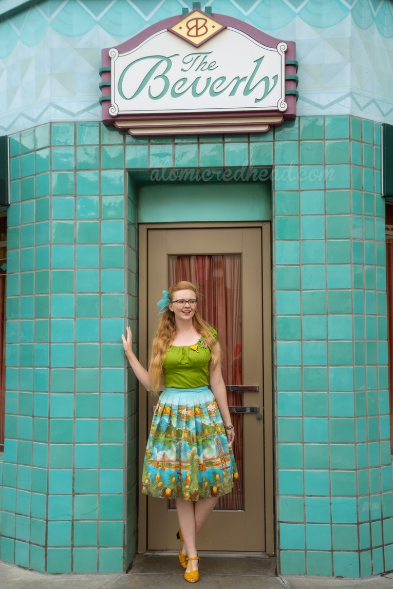 Myself standing in the doorway of a blue tile building, wearing a green peasant top, with a D shaped brooch, and a poppy flower brooch, and a skirt featuring images of the San Fransisco-Oakland Bay Bridge, Catalina, and Mission Santa Barbara, a blue scarf is tied in my hair, and yellow shoes.