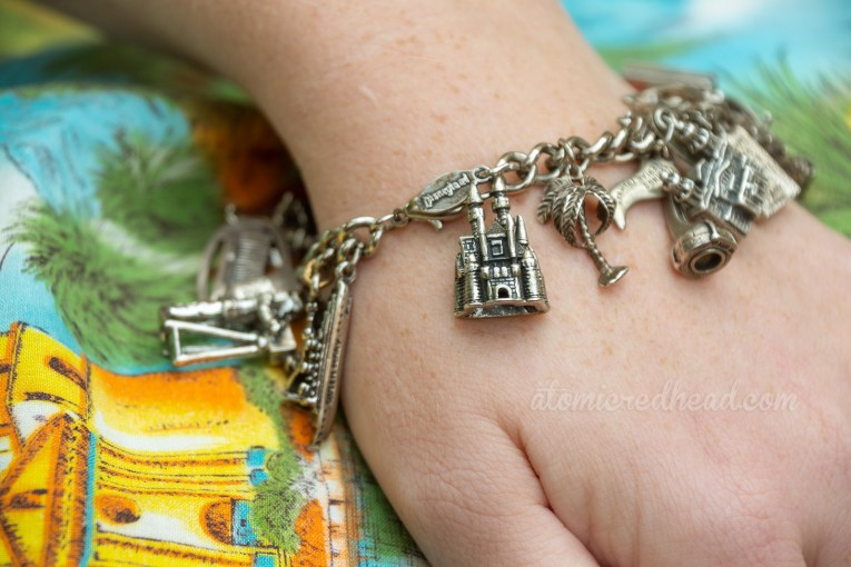 Close-up of my charm bracelet, which features Sleeping Beauty Castle, a palm tree, the Palm Springs Arial Tram, and others peeking out of view.
