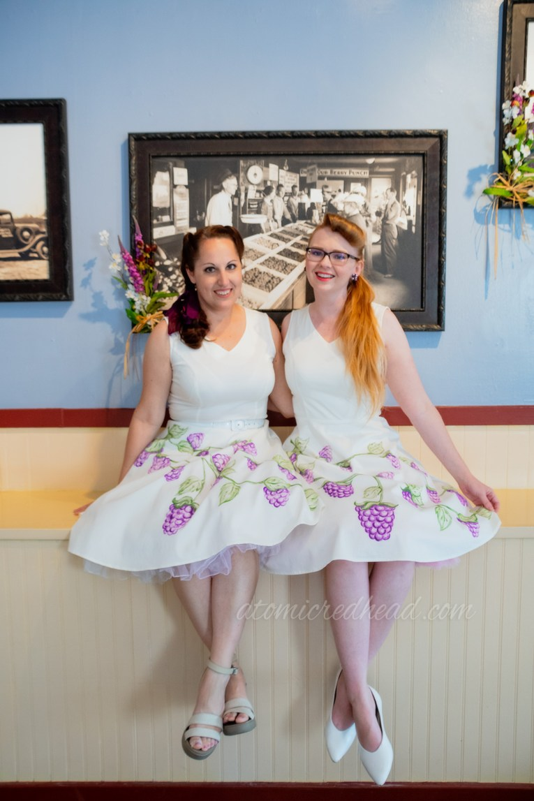 Kiley and I sitting on inside Town Hall, with old photographs of Knott's Berry Farm in the background, wearing the same thing, a white dress with painted boysenberries.