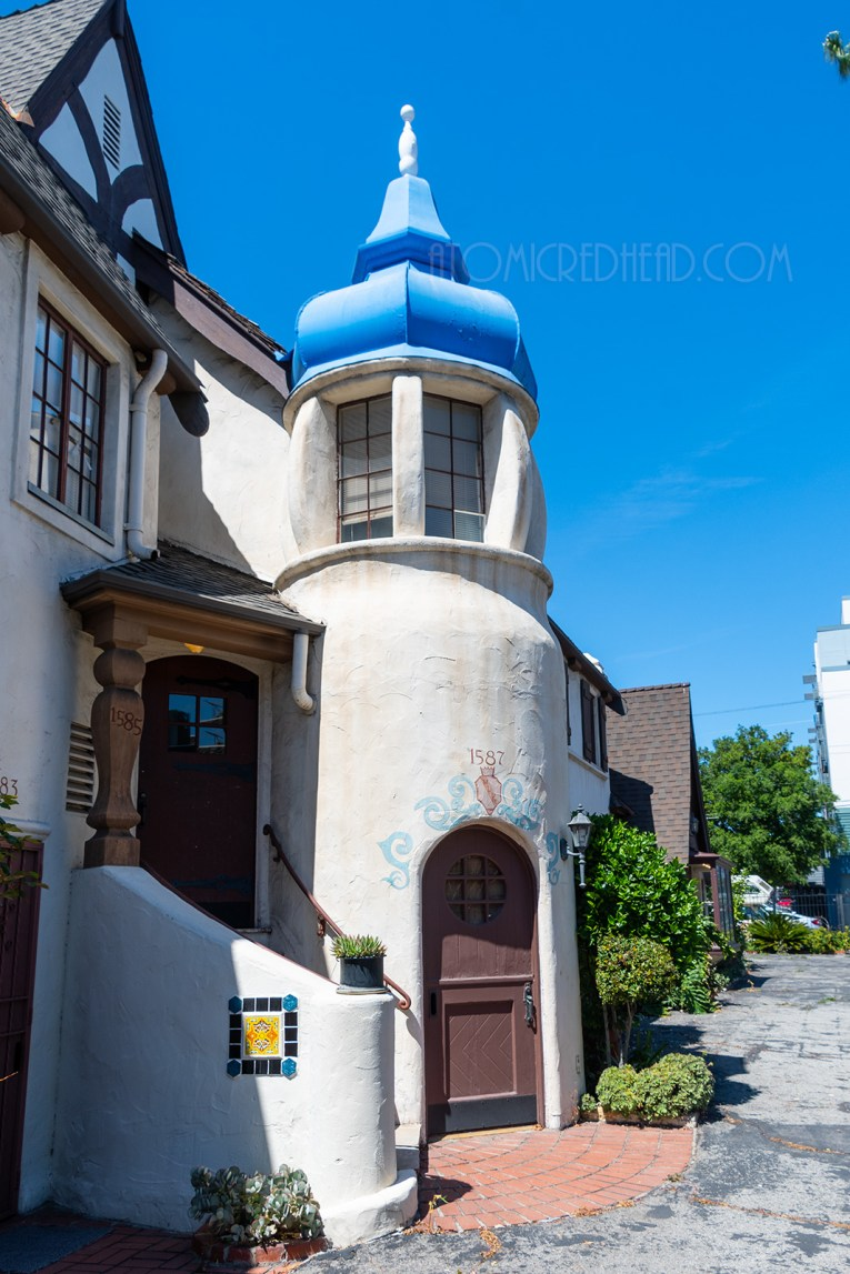 A white stucco tower with a blue swirling roof.
