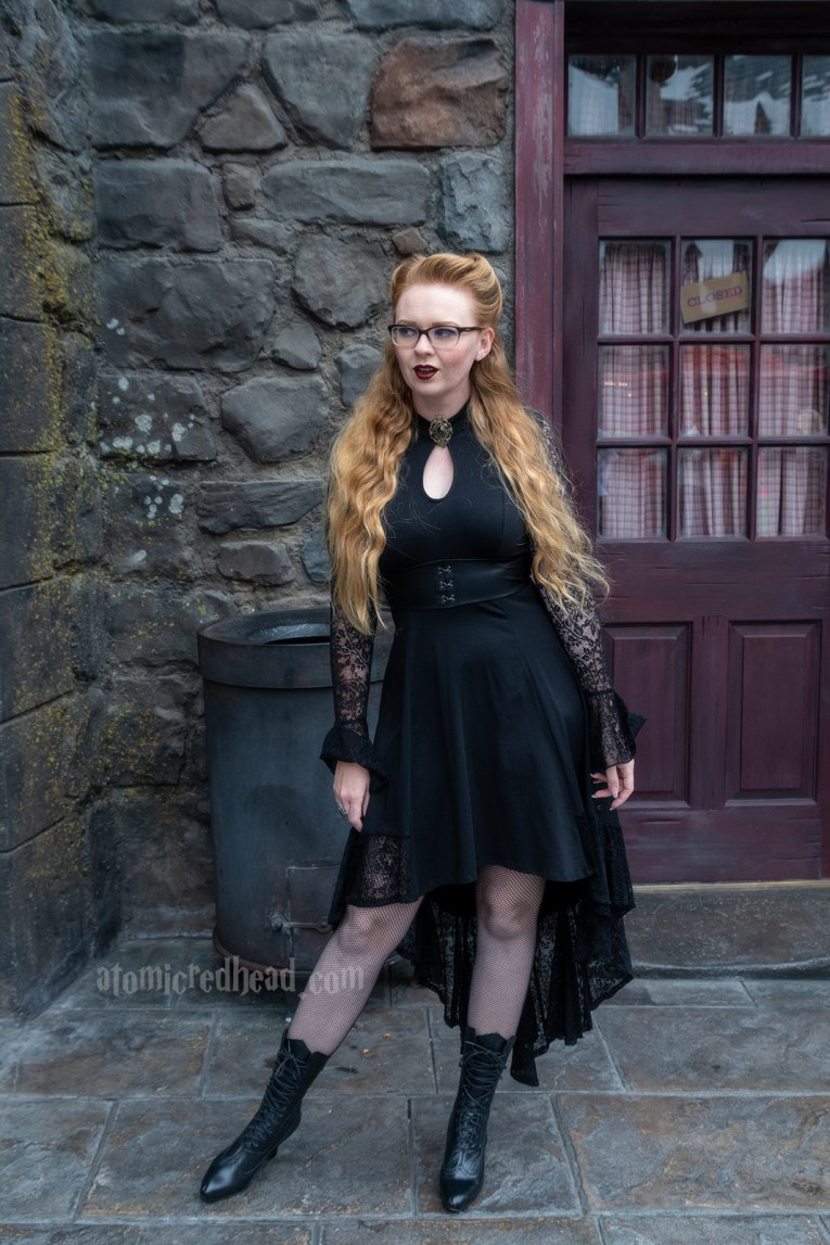 Myself standing against a dark stone building with a maroon colored door, wearing a black high-low dress with lace sleeves, and a key hole cut out at the neck, that features a gold brooch with a purple stone, fishnets, and a mid-calf hight Victorian style lace up boots.