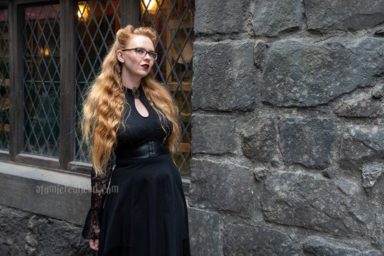 Myself standing against a dark stone building, with diamond pane windows, wearing a black high-low dress with lace sleeves, and a key hole cut out at the neck, that features a gold brooch with a purple stone, fishnets, and a mid-calf hight Victorian style lace up boots.