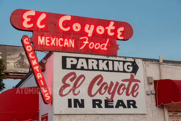 "The red neon sign outside which reads ""El Coyote Mexican Food"""