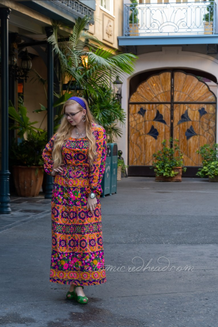 Myself, wearing a purple, yellow, pink, and green psychedelic printed maxi dress with a purple scarf in my hair, in New Orleans Square.
