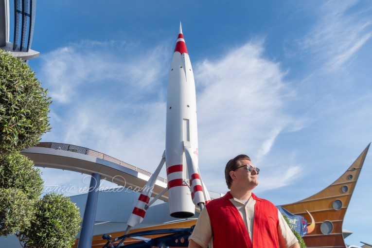 Patrick, wearing a red and white shirt and white pants stands next to the towering red and white rocket of Tomorrowland.