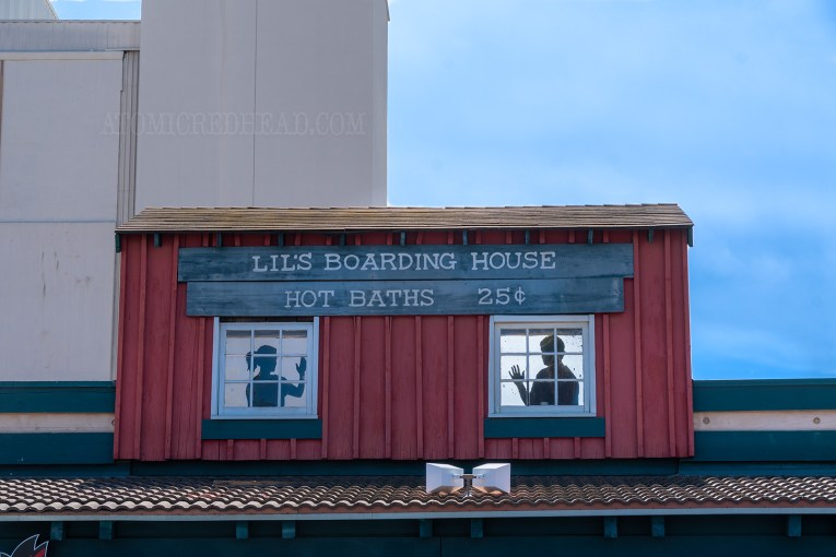 Above the real establishments, faux ones exist, like this Lil's Boarding House, advertising hot baths for 25 cents. Silhouettes of a man and a woman sit behind faux windows.