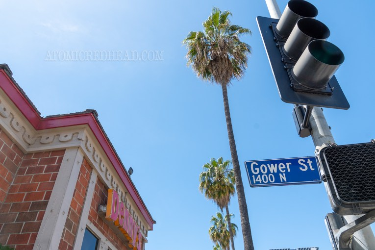 A western themed Denny's sits on the corner of Gower and Sunset, the street sign for Gower visible.