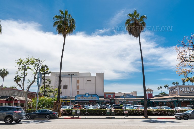 Gower Gulch, a strip mall of western themed facades, with two tall palm trees out front.