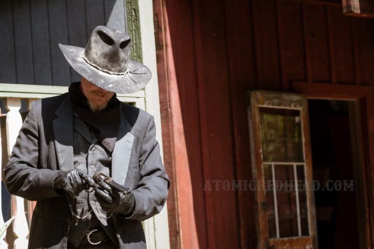 Clay Mayfield, a cowboy dressed all in black inspects his gun.