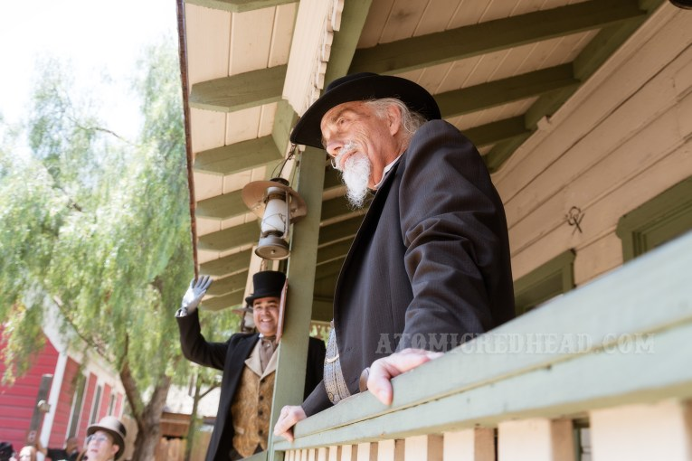 Judge Roy Bean, the town judge, an older gentleman, with a white mustache and goatee, dressed all in black, stands on the Town Hall porch.