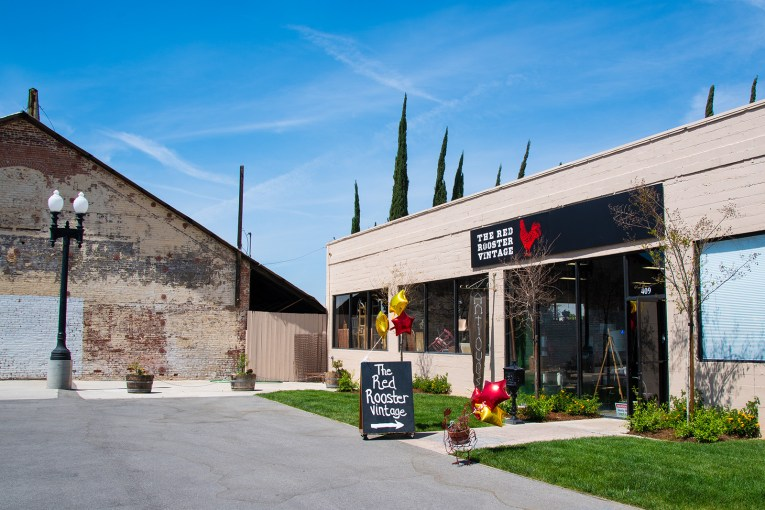 """A pale tan building features a large black sign that has white text reading """"The Red Rooster Vintage"""" and an image of a red rooster stands next to it."""