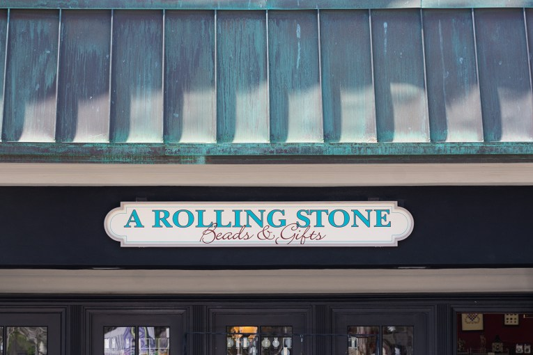 """A copper roof that has turned green sits atop a white sign reading """"A Rolling Stone Beads & Gifts"""""""