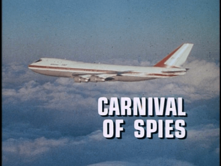 "Screencap: A plane flies through a blue sky, white text reads ""Carnival of Spies"""