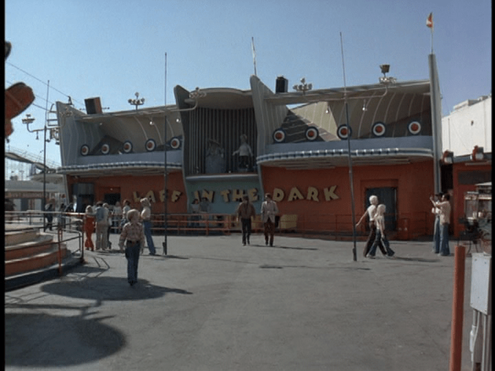 "Screencap: A streamline modern looking building painted orange and blue features large yellow letters reading ""Laff in the Dark"""