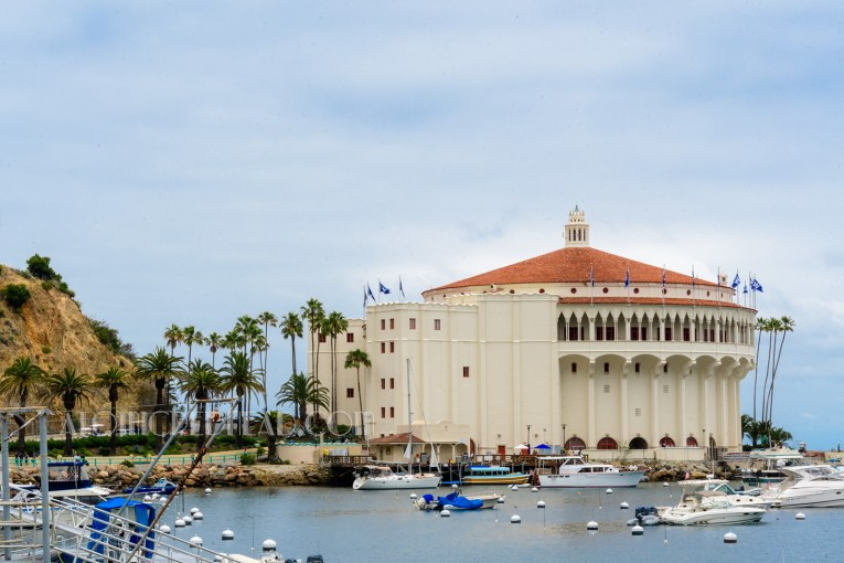 The Casino Building as seen from the beach, a cream colored circular building with a red colored Spanish tile roof. Arches grace the upper floor and look toward toward the ocean.