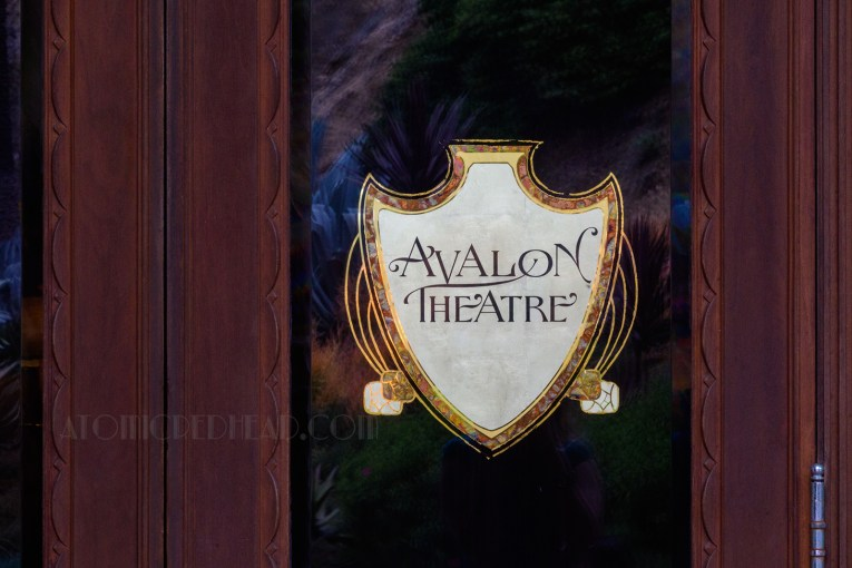 "Close up of a painted white shield with the words ""Avalon Theatre"" on it, edged in gold, on the door into the theatre."