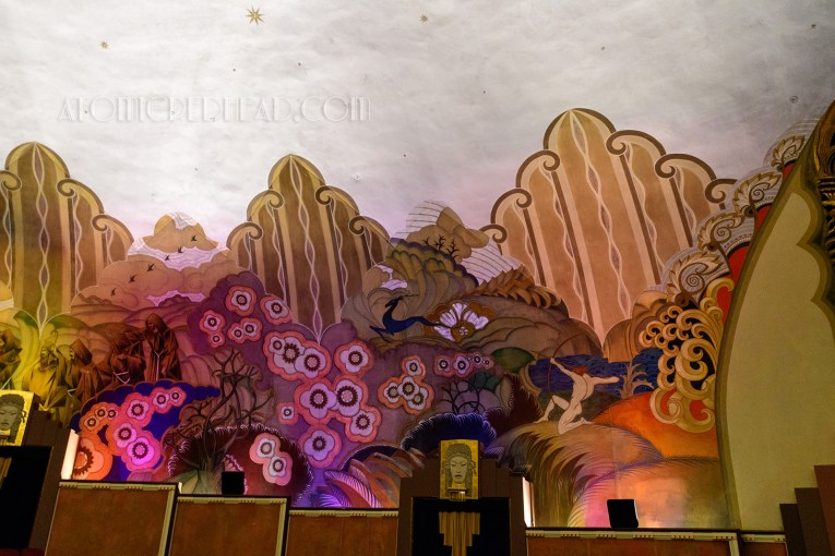 Inside the theatre, a massive painting encompasses the seating area, depicting a fanciful history of California, here a nude man shoots a bow and arrow into an art deco wilderness.